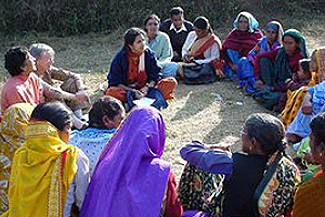 A group of village women sitting in a circle.