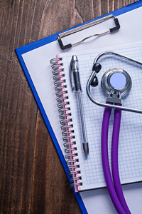 A stethoscope on a paper pad.